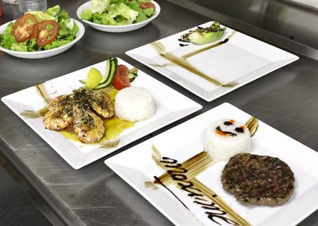 comida italiana: comida italiana: camarones, verduras y hamburguesa en plato cuadrado Foto de archivo
