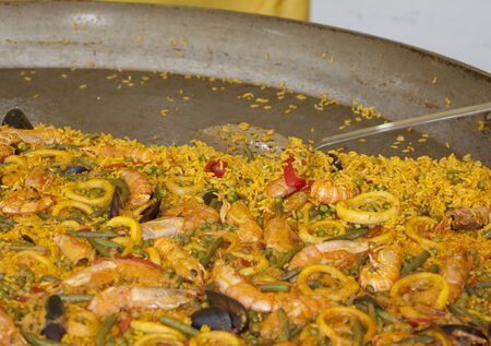 yellow paella valencian with rice, fish, meat and vegetables