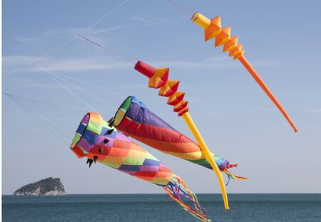 windy day: colored kites in a windy day in ligurian riviera, italy Stock Photo