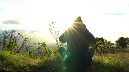 Man hermit meeting up sun rise on the edge of mountains. Doing meditation in sun light. Putting on hood Stock Photo