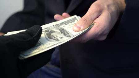business man giving money to hand in black gloves, crime concept bribe
