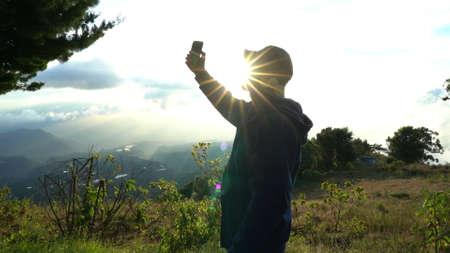 Mann, der selfies in den bergen macht, wenn die sonne schöne landschaft aufgeht. Erinnerungen an den Urlaub
