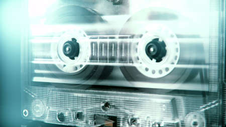 Audio cassette tape in use sound recording in the tape recorder. Vintage music cassette with a blank white label, playing back in the player. 4K, static camera