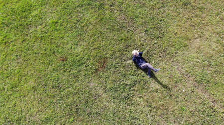 Bird eye view shot of a caucasian or Hispanic man laying down on green grass on a sunny day. relaxing CONCEPT aerial shot