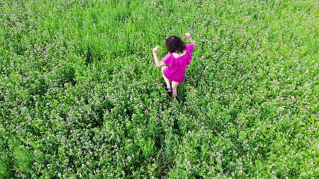 sexy girl in red dress dancing outdoors in green field, touching hair and moving seductive, fun, pleasure, enjoyment, freedom concept, shot from drone, top view, above