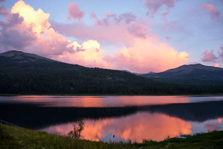 pink clouds reflection in the lake in Eastern Kazakhstan in summertime with mountains on background Stock Photo