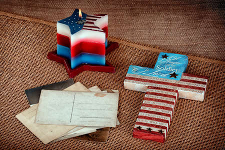 Patriotic Background with candle cross and postcards on canvas Stock Photo
