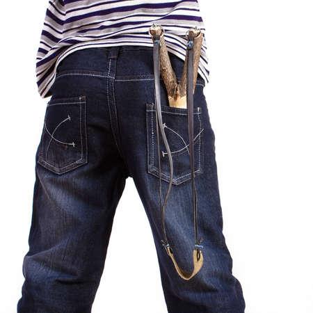ni�o parado: muchacho que se coloca de nuevo con una honda en el bolsillo Foto de archivo