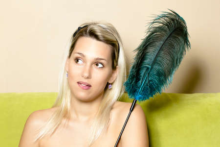 pensive portrait of a woman with an ostrich feather when cleaning photo
