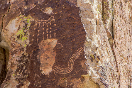 Rains falls on a missing piece of an ancient map with a river flowing off the bottom. A sad case of vandalism in Basin and Range National Monument, Lincoln County, Nevada, USA.