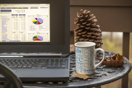 Laptop and coffee mug on outside table