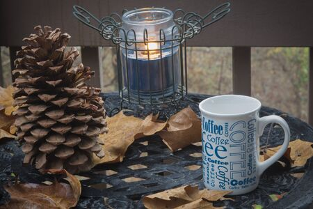 lit: Coffee Mug on outside table with a lit candle Stock Photo