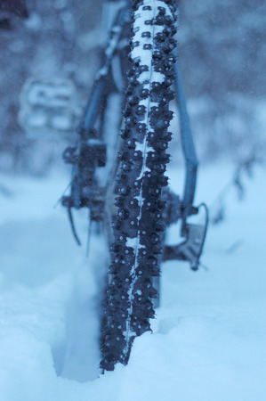 Mountain biking in the winter, Close-up on a background of falling snow Stock Photo