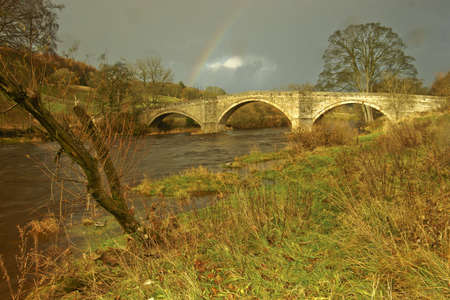 old packhorse bridge: After a heavy storm,  sunlight briefly lights up the old packhorse bridge on the Bolton Abbey Estate,in Nidderdale, Yorkshire  Part of the Duke of Devonshires Estates