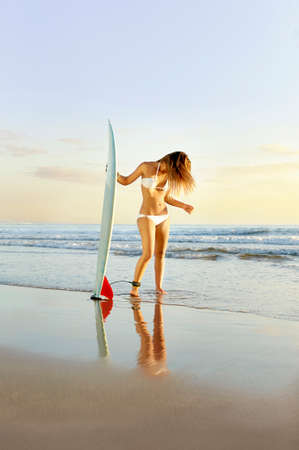 Young attractive surfer girl on beach with surfboard at sunrise photo