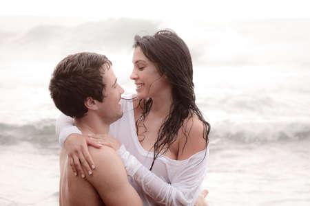 romantic couples: Pareja joven sexy playa romanticismo afecto besarse feliz sonriendo