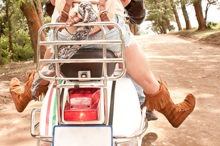 Young beautiful sexy couple in love traveling together on scooter photo