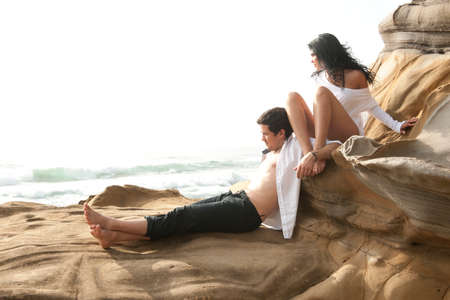 Young beautiful sexy couple in love flirting at the beach