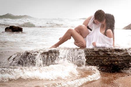 verliefd stel: Jonge sexy paar kussen omhelzing romantiek oceaan rotsen strand