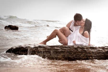 besos hombres: Pareja joven sexy besar abrazo romántico rocas del océano playa