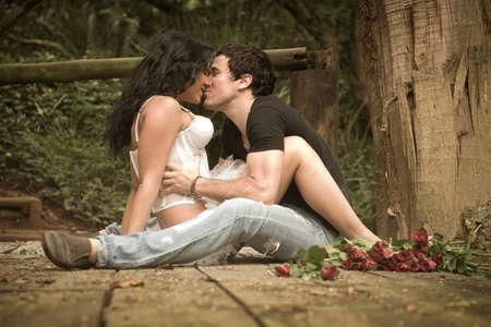 baiser amoureux: Beau jeune couple sexy en amour flirter ensemble sur terrasse en bois Banque d'images