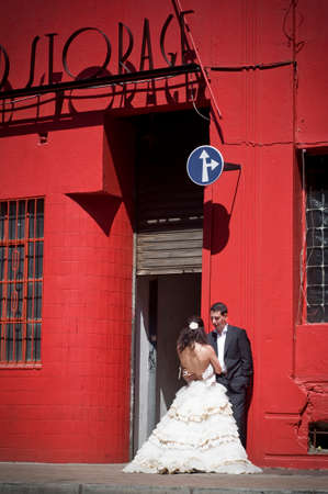 Happy bridal couple standing on sidewalk below tall red building  photo