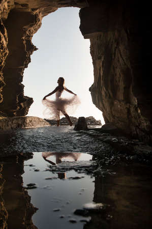 newly weds: Young beautiful woman having fun dancing under rock archway