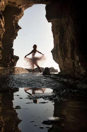 Young beautiful woman having fun dancing under rock archway