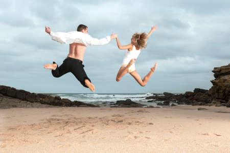 Young beautiful couple having fun flirting together at the beach Фото со стока