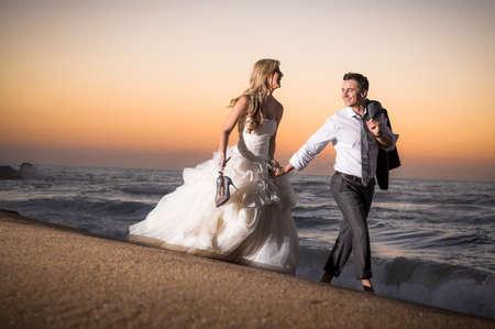 Young beautiful bridal couple having fun together at the beach Фото со стока