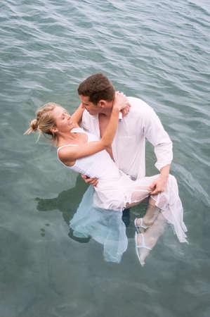 Young beautiful couple having fun flirting together at the beach Standard-Bild