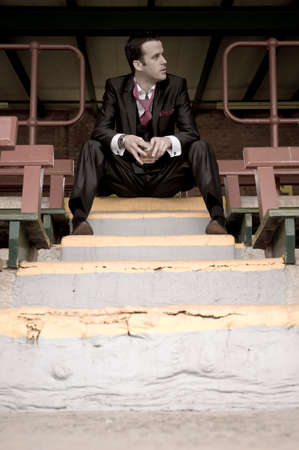 concrete steps: Young handsome man sitting on concrete steps in suit Stock Photo