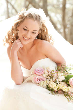 formal clothing: Young beautiful bride smiling happily with bouquet of flowers
