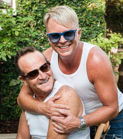 early 40s: Two handsome gay men enjoying time together outdoors in their garden