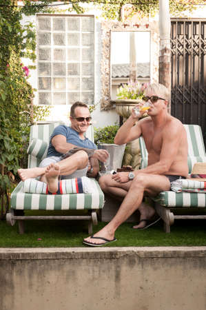 homosexuales: Dos hombres gay guapo disfrutando de tiempo juntos al aire libre en su jard�n