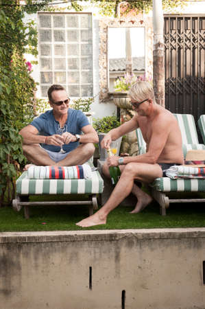 mid thirties: Two handsome gay men enjoying time together outdoors in their garden