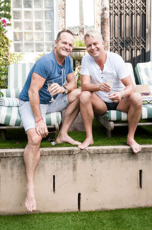Two handsome gay men enjoying time together outdoors in their garden
