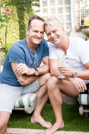 Two handsome gay men enjoying time together outdoors in their garden photo