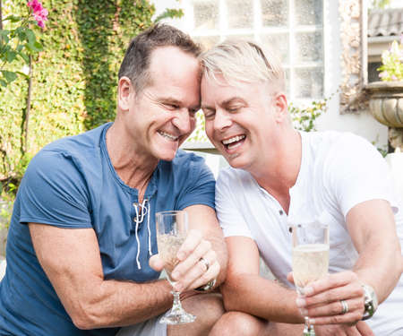 amor gay: Dos hombres gay guapo disfrutando de tiempo juntos al aire libre en su jardín