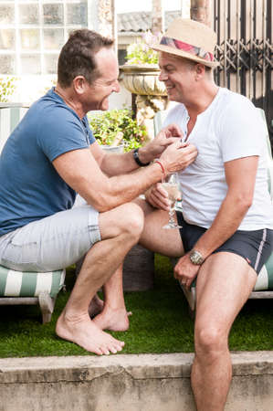 prime adult: Two handsome gay men enjoying time together outdoors in their garden