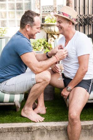 Twee knappe homo's genieten van tijd samen buiten in hun tuin Stockfoto