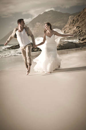 Happy beautiful couple running along beach together with mountain in background photo