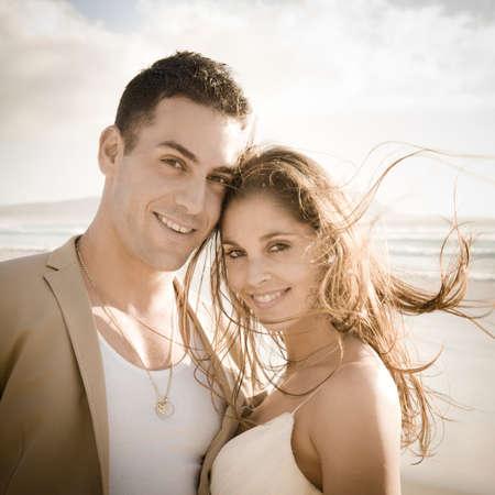 couple  amoureux: Mari�s Handsome d�tente sur la roche � la plage en regardant la cam�ra Banque d'images