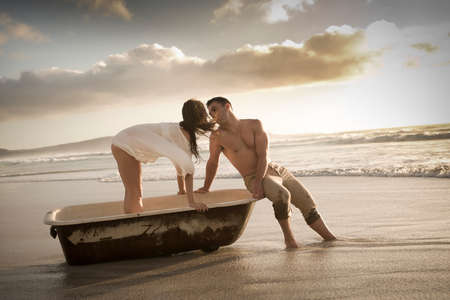 woman in bath: Happy young couple having fun with old vintage bath on the beach at sunrise