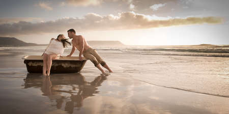 Happy young couple having fun with old vintage bath on the beach at sunrise photo