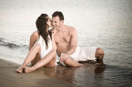 novios besandose: Feliz pareja de j�venes sentados juntos se divierten en la orilla del agua