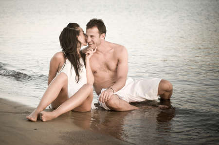 flirting women: Young happy couple sitting together having fun at waters edge
