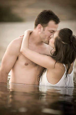 sexy couple kissing: Young happy couple sitting together having fun in body of water Stock Photo