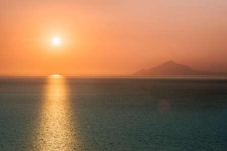 Sunrise over the ocean with burnt orange sky Фото со стока