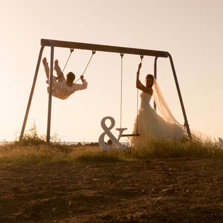 swing set: Silhouette of young couple playing on swing set at sunset  Stock Photo